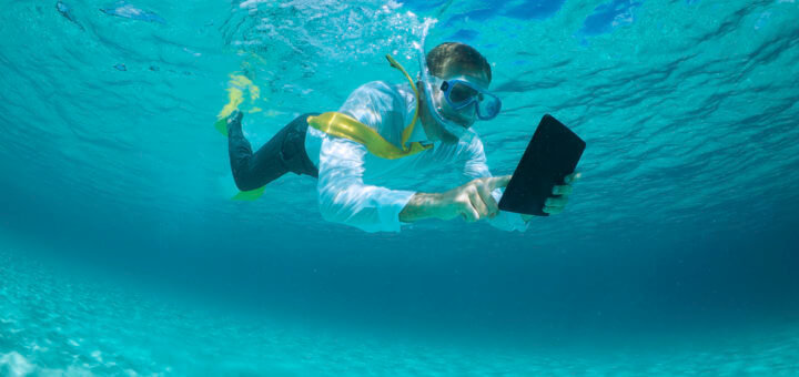 Businessman snorkeling in tropical blue seas using a digital tablet